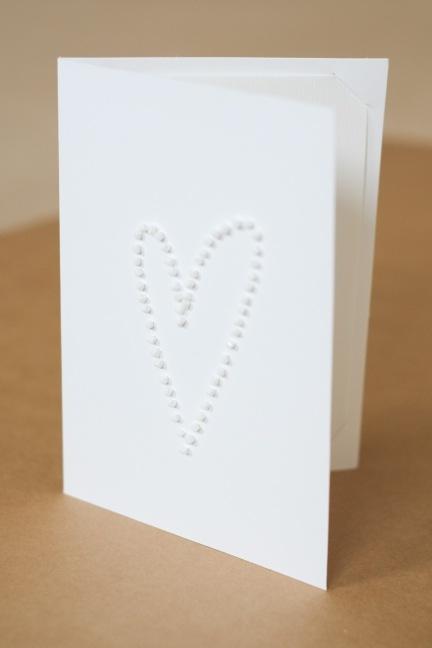 Horizontal, hand-sewn white beads wedding invitation.