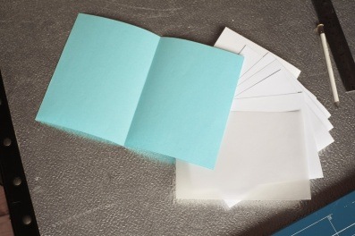 Fold each trimmed sheet in half.